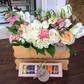 Ящик с цветами и коробка макаронов